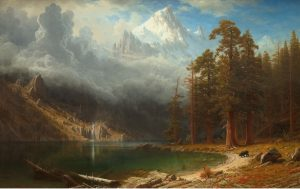 A beautiful scene with mountains and tall pine trees in the background and a lake with a small waterfall in the foreground.