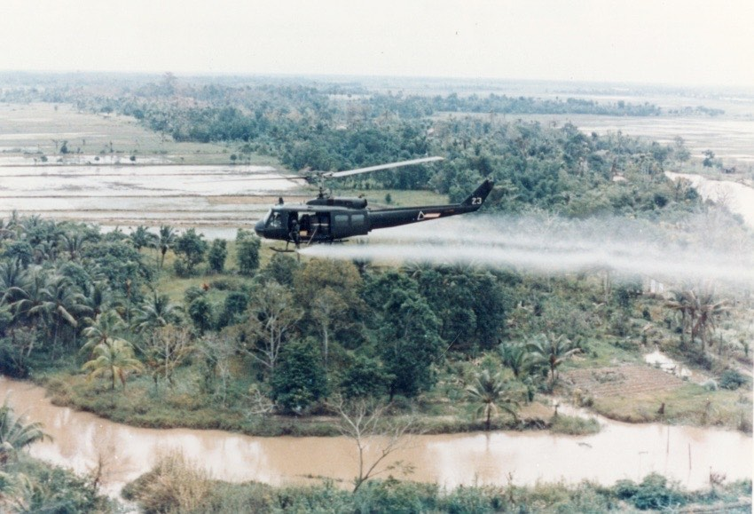 Helicopter Flying Overhead a Forest Misting Agent Orange Below