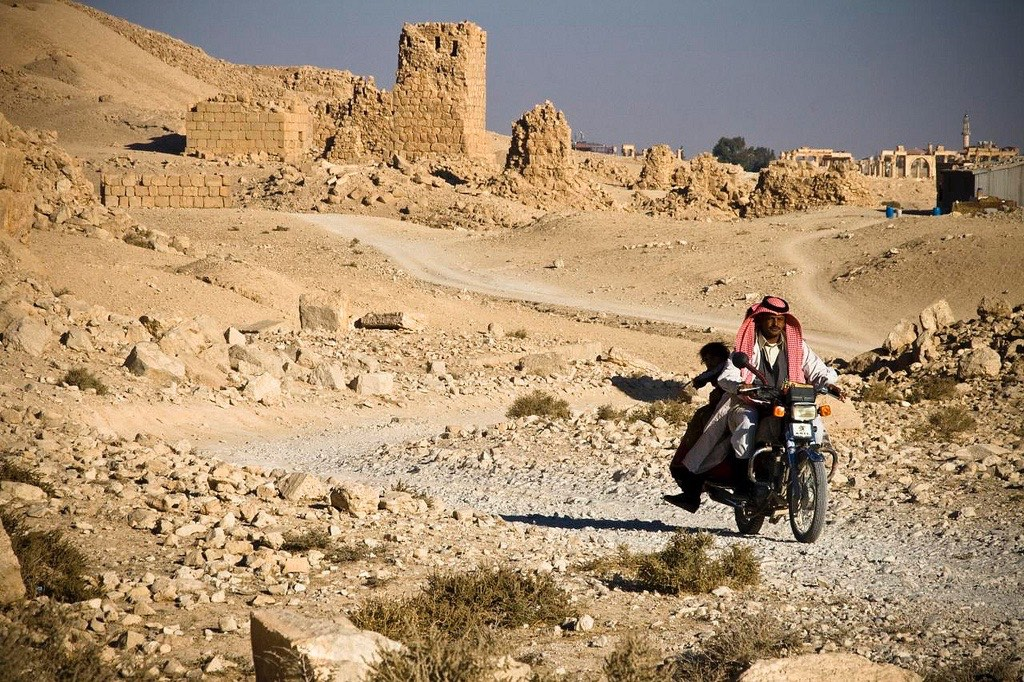 Man riding motorbike through Syrian desert