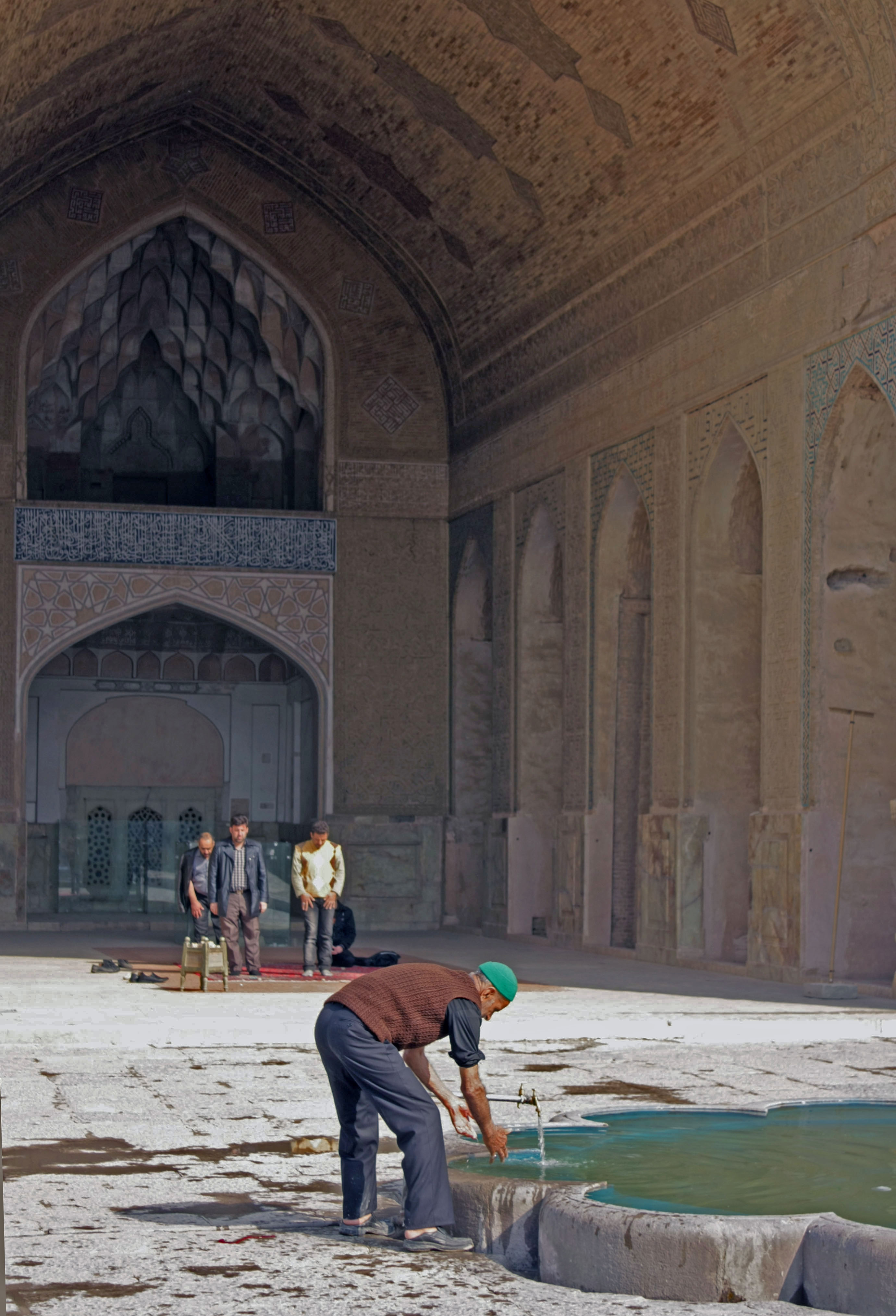 Image of Man performing ablution, and men praying in the background, in the courtyard of a mosque in Iran.