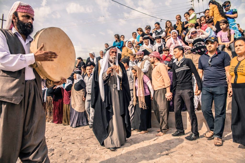 """Image of Yazidi Ceremony: 'Sons of the Peacock Angel' Prayers and ceremonies during the annual spring celebrations dedicated to the shrine of Mohamed Rashan where many Yazidi's families, each from different villages, pay their visit to the servant of the temple and his family offering him food and donations. This is one of the most important celebrations of Yazidis. They camp together in wide grass fields, pray and dance typical music played by the Kawals using the 2 typical instruments, the Daf (frame drum) and the Shabbabi (flute)."""" Caption and image by Giulio Paletta, LUZ Photography, All rights reserved."""