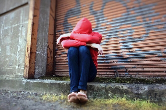 person in red hoodie with head down, arms crossed, and seated in front of a graffit'di door