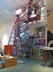 Robbie Conal installs a collage of posters