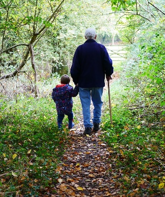 a grandfather walking with his grandson in the woods