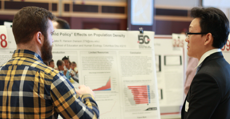 student presenting poster to another student at poster symposium