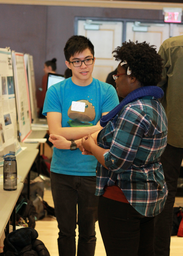 student presenting poster to audience member