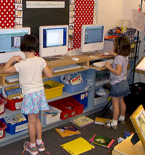 Two first grade female students using computers in a classroom