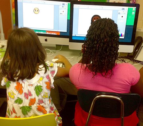 Two girls create digital illustrations on desktop computers