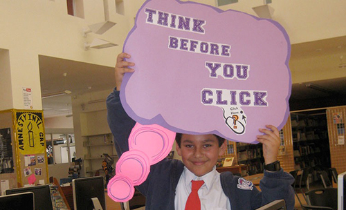 """Student holding sign with """"Think before you click"""" slogan"""