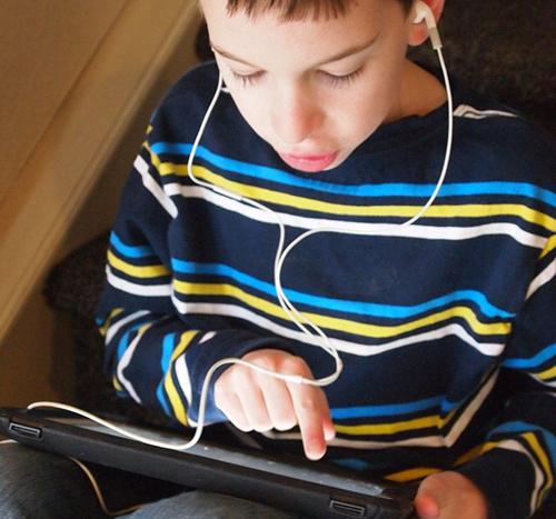 Student using iPad and listening on headphones