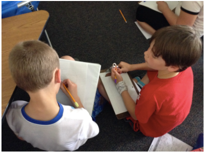 Two students with writing materials and paper involved in a discussion