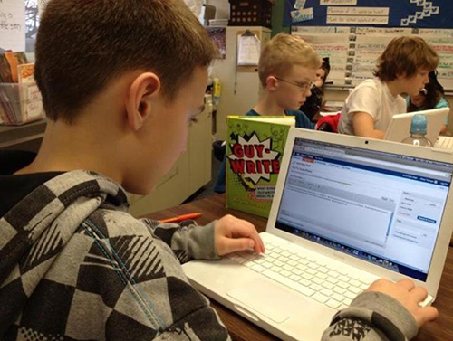Student writing a blog post on a laptop