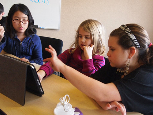 Three girls use an iPad in a classroom