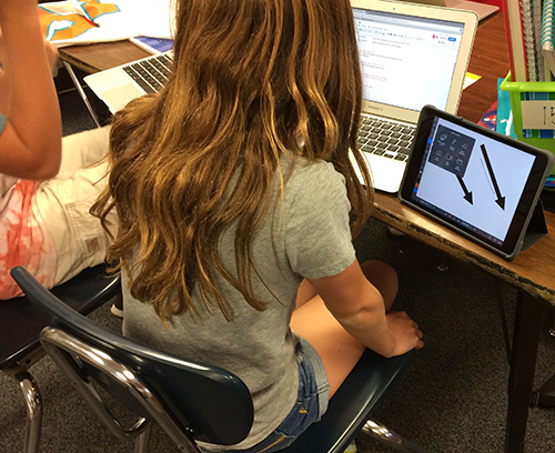 Students using laptops and mobile devices in classroom