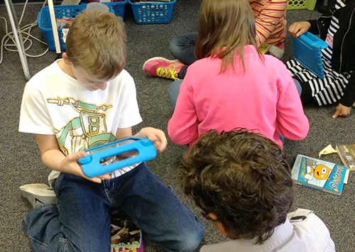 Students sitting on classroom floor using electronic devices