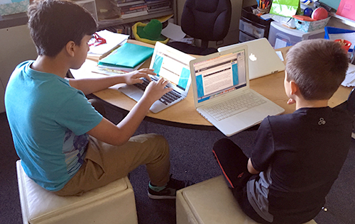 Two students writing on their laptops