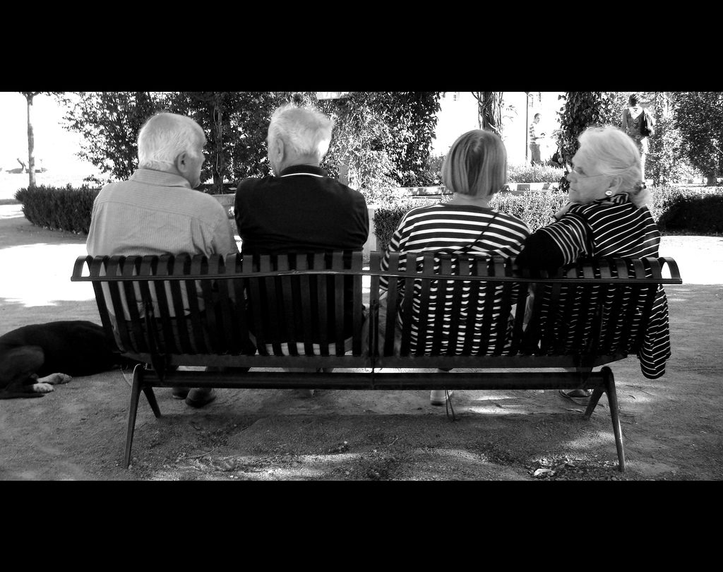 a black and white phote of two elderly couples on a bench