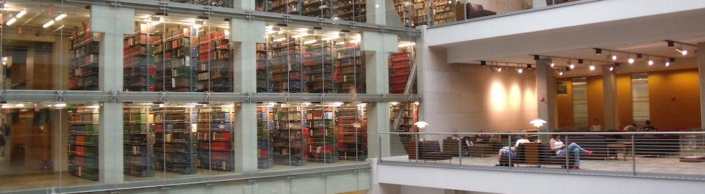 Students working and looking across the atrium to several floors of library stacks.