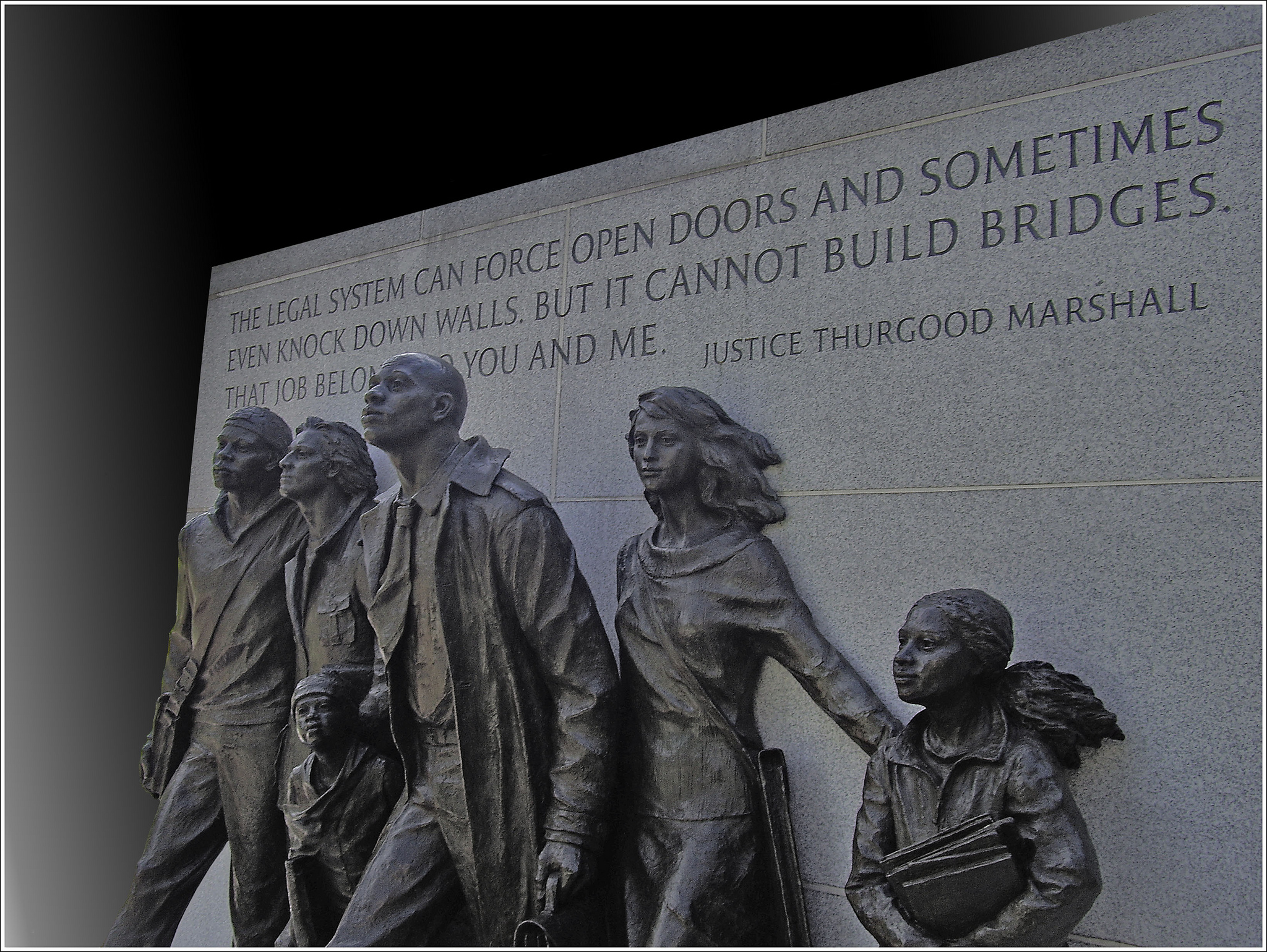 "Statues of 4 adults and 2 children in front of a wall with the engraved quotation from Justice Thurgood Marshall that reads, ""The legal system can force open doors and sometimes even knock down walls, but it cannot build bridges. That job belongs to you and me."""