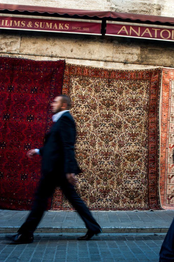 image of carpets hanging on Istanbul street,man walking