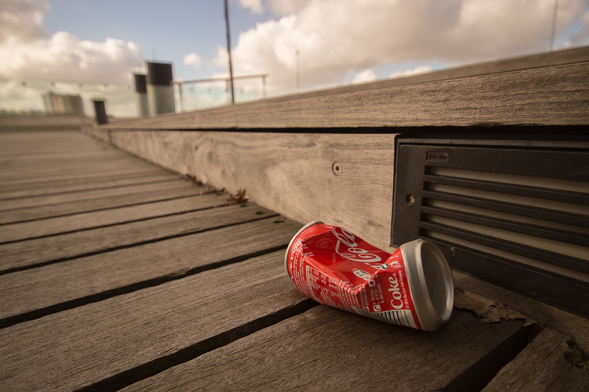 crushed Coke can laying on a wooden dock under a cloudy sky