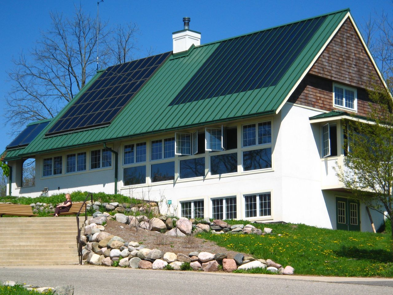 house with roof showcasing a standard solar panel with many separate cells on top of the roof and a one panel that mimics the long, straight roof tiles.