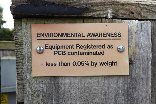 "sign bolted to a wooden post that reads ""environmental awareness, equipment register as PCB contaminated, less than 0.05% weight."""