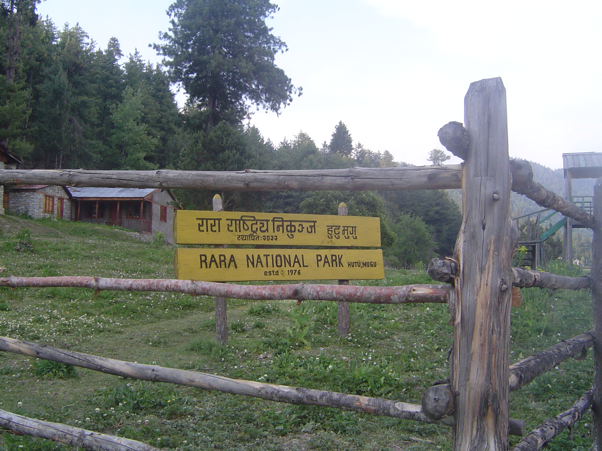 Rara National Park sign showing through a wooden fence with cabins and forest land in the landscape