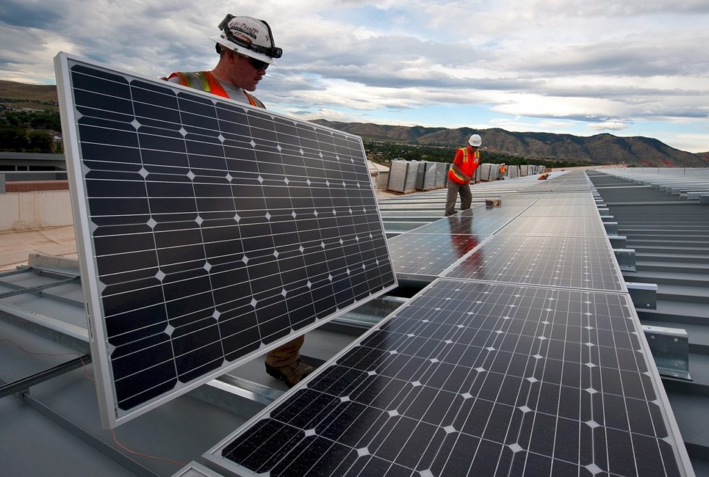 Two workers with reflective vests work on a rooftop to construct a photovoltaic system.